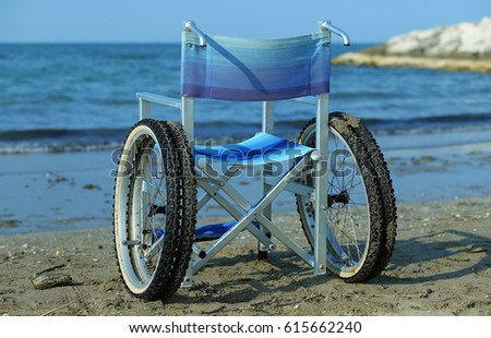 wheelchair by the sea in summer with large wheels to go on the sand