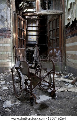 wheelchair in old abandoned hospital - stock photo