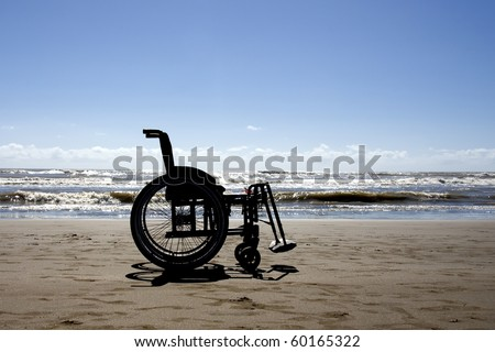 Wheelchair in the beach, backlight - stock photo