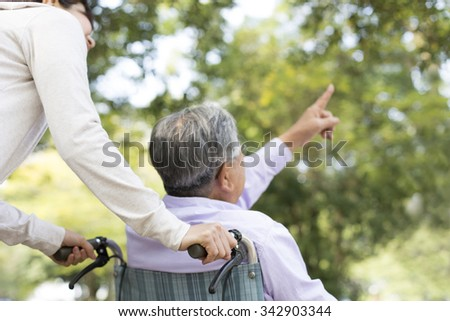 Wheelchair old man and a helper - stock photo