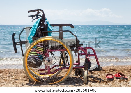 wheelchair on the beach against blue sea in summer - stock photo