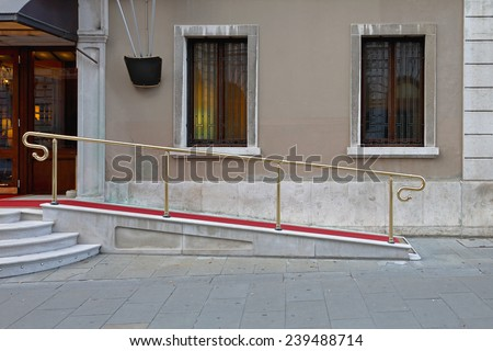 Wheelchair ramp with red carpet for easy access in building - stock photo
