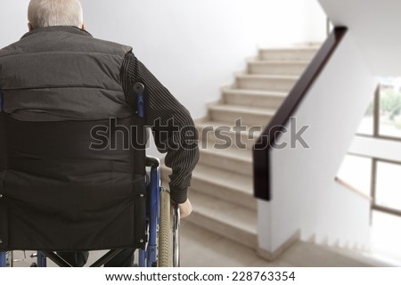 Wheelchair user in front of staircase barrier - stock photo