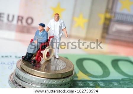 Wheelchair user with nursing staff and money / wheelchair user - stock photo