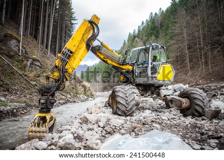 Wheeled excavator in a river in the autumn forest mountains - stock photo