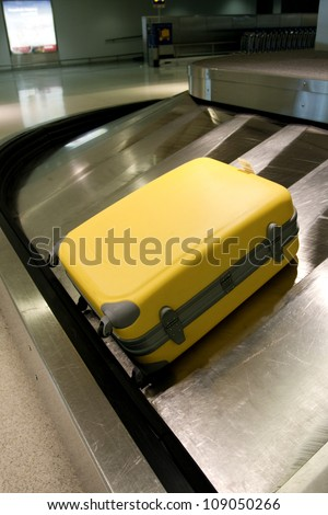 Wheeled suitcase on baggage carousel in airport