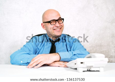 Wheeler dealer businessman. Smiling businessman at office desk with telephone.