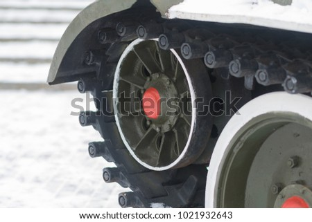 Wheels and tracks of an old tank on snow
