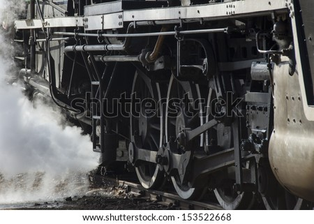 Wheels of a steam train standing at the station while it loads passengers and build up pressure before taking off on a trip - stock photo