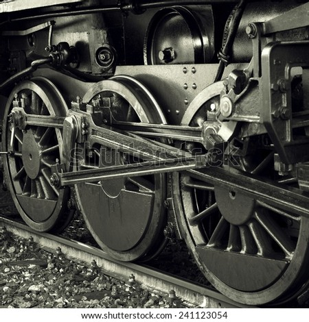Wheels of a very old steam engine - stock photo
