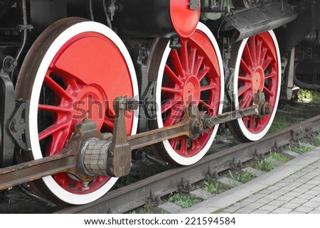 Wheels of steam locomotive on rails closeup shot at an angle