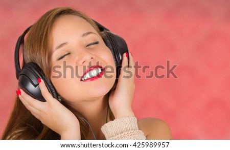 When a song is so good you can feel it, woman with headphones, eyes closed and hands on it