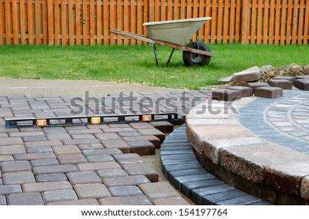 When building a patio prepare to use level and barrel constantly, patio island have polymeric sand laid and job completion almost done when final pavers cut and placed - stock photo