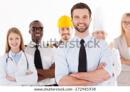 When I grow up I will be a businessman. Confident young man in shirt and tie keeping arms crossed and smiling while group of people in different professions standing in the background - stock photo