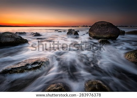 When night comes - rocky beach long exposure seascape after sunset - stock photo