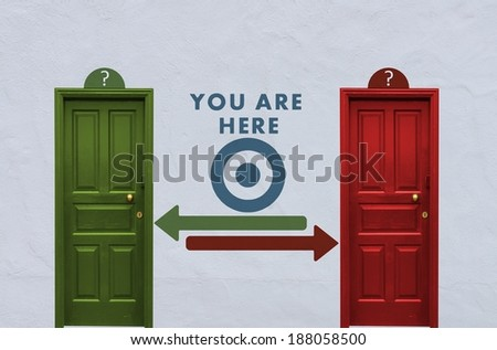 where is the you are here behind the red or the green door? A concept image showing two closed doors with a you are here symbol painted on the wall in between - stock photo