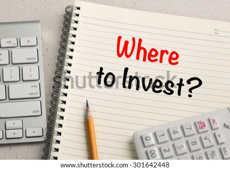 where to invest concept, with calculator and desk background - stock photo