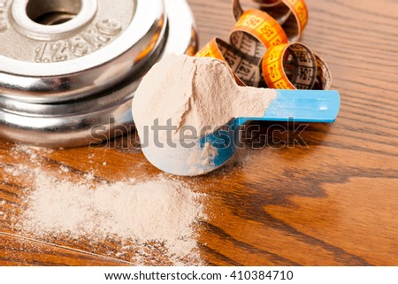 Whey protein powder in measuring scoop, meter tape and dumbbell on wooden background. - stock photo