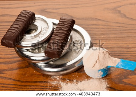 Whey protein powder in measuring scoop, protein bar, meter tape and dumbbell on wooden background.