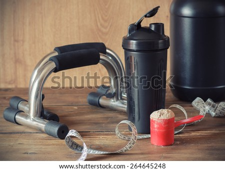 Whey protein powder in scoop and plastic shaker on wooden background. Selective focus, shallow DOF - stock photo
