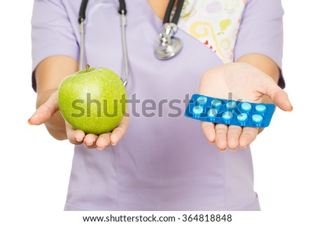 Which one do you choose? Cropped closeup of a female doctor holding an apple and pills to choose in her hands - stock photo