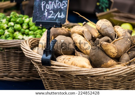 Whicker basket filled with sweet potatoes and a sign.  Brussels Sprouts in a second basket in the background. - stock photo
