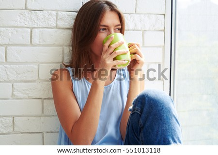 While sitting on the window-sill and drinking a cup of coffee in the morning young modern girl is thoughtful and focused for a while