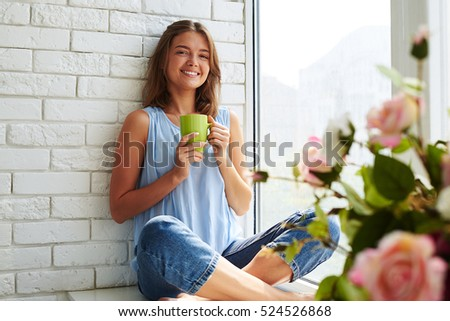 While thinking about plans a young pretty girl smiling softly and frankly. Sitting on the window-sill and drinking a cup of aroma coffee