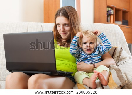 Whiner woman with a crying baby, working on the Internet with a laptop at home - stock photo