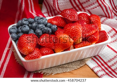 Whip Cream, strawberries and blueberries combined to look like the american flag and placed in a ceramic tray  for a 4th of july themed party, on a wooden table and rustic towel