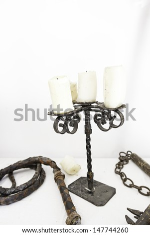 Whip the Inquisition and candlestick, torture detail medieval instrument, pain and death - stock photo