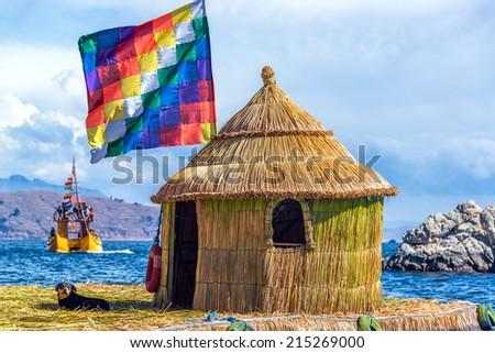 Whiphala flag on a hut on a floating island on Lake Titicaca near Copacabana, Bolivia - stock photo