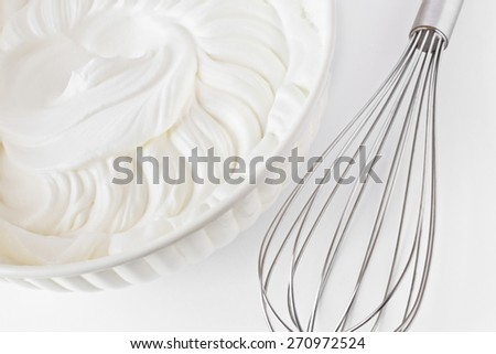 Whipped cream and  a whisk - stock photo