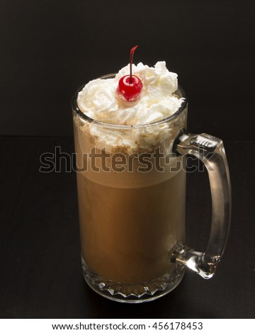 Whipped cream cherry ice cream and root beer in a mug.Delicious Soda Float/Refreshing beverage ready to be enjoyed