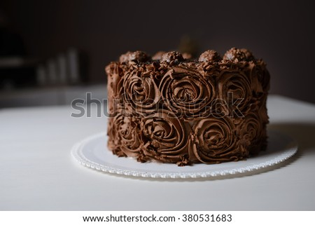 Whipped cream chocolate cake with rose flower decoration.