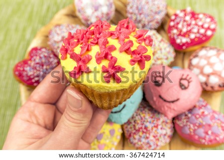 Whipped cream decorated muffin held in hand - Image with a home made cupcake, decorated with yellow cream and flower shaped red frosting, held in hand in front of the camera. - stock photo