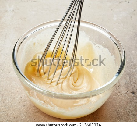 whipped egg yolks with sugar in a glass bowl - stock photo
