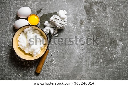 Whipped eggs in a bowl with a whisk. On a stone background. Free space for text . Top view - stock photo