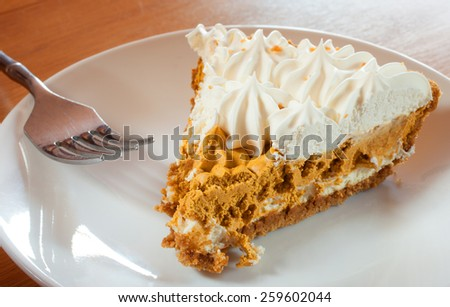 Whipped pumpkin pie slice and fork on a white plate