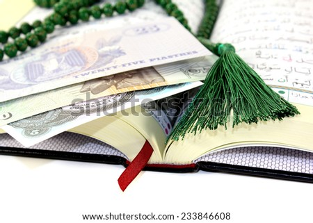 whipped Quran with Egyptian currency before light background - stock photo
