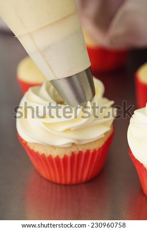 Whipped white frosting being applied to a vanilla cupcake - stock photo