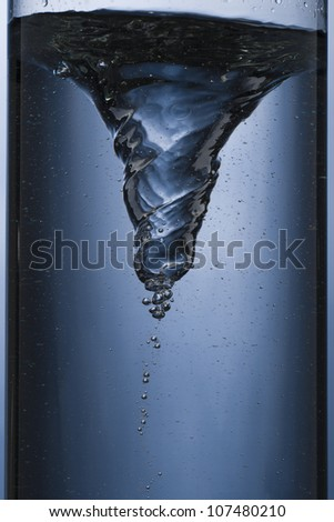whirlpool in a column of water - stock photo