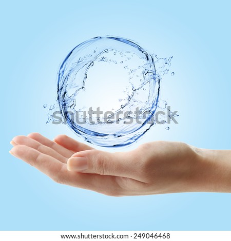 Whirlpool in hand on light blue background - stock photo