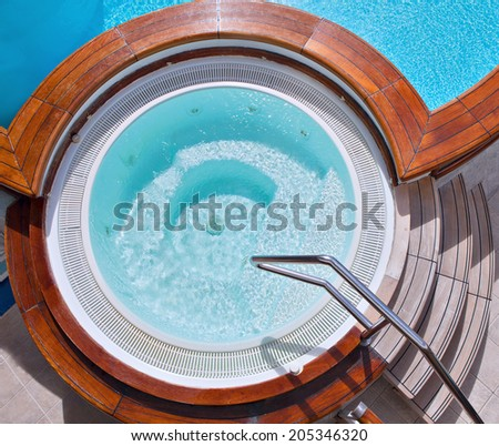 Whirlpool jacuzzi with wooden steps and pool on the deck of a cruise ship. View from above. See my other shots from cruise ship. - stock photo