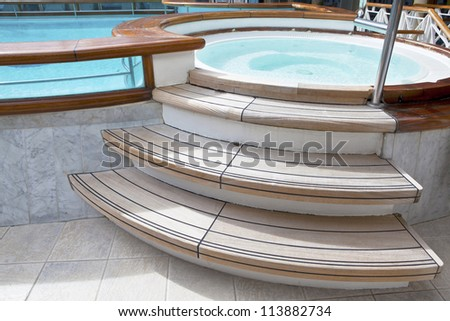 Whirlpool jacuzzi with wooden steps and pool. Selective focus on steps - stock photo