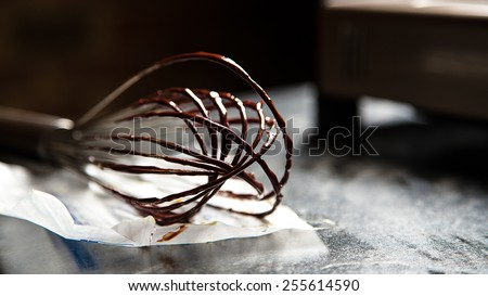 Whisk with gooey chocolate frosting - stock photo