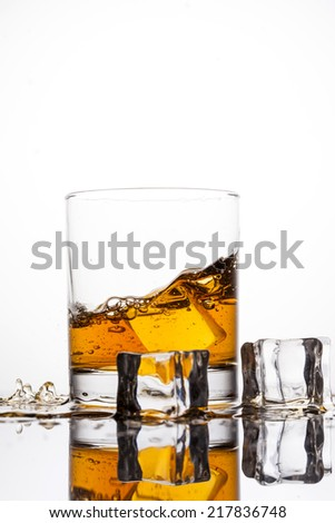 Whisk?y splashing in glass on a white background