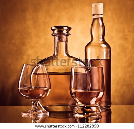 Whiskey and cognac bottles with filled glasses - stock photo