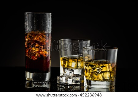 whiskey and cola with ice on a black background