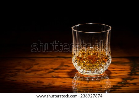 Whiskey and Wood - Liquor in a diamond-cut tumbler on a textured wooden table.  Spot light focused on the glass.  Copy space on left.  Upper frame fades to black. - stock photo